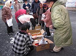 牡鹿エリア仮設住宅での、年末物資提供のようす。皆で分け合う、生協の班共同購入と同じ風景です。
