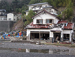 石巻市の月の浦では、今でも満潮時は冠水し、高台にある避難所の民家に入るには潮が引くのを待つしかない状態です。。
