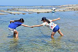 海で遊び始めた子どもたち